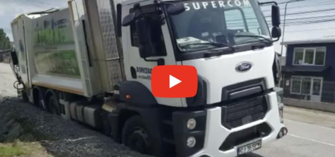 """Mașină de gunoi de la SUPERCOM, """"înghițită"""" de șosea. VIDEO"""